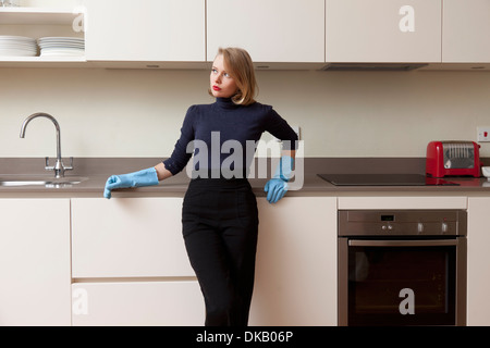 Woman leaning against kitchen cabinet - Stock Photo