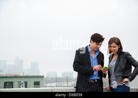 Couple listening to shared earplugs on city rooftop - Stock Photo