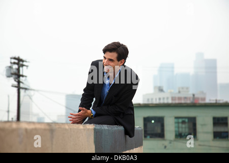 Happy young man on city rooftop - Stock Photo