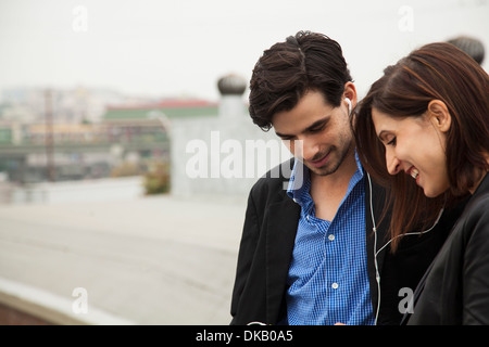 Couple listening to shared earplugs on city roof