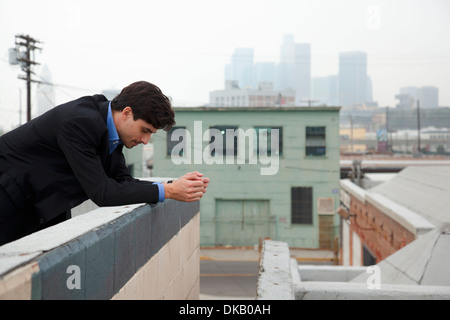 Unhappy young man looking down from city rooftop - Stock Photo