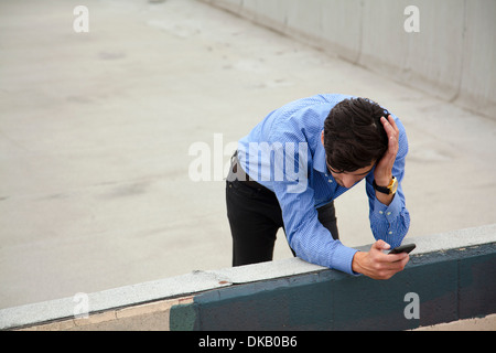 Anxious young man leaning on wall on city rooftop - Stock Photo