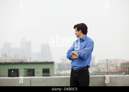 Young businessman with folded arms on city rooftop - Stock Photo