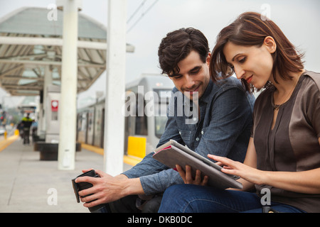 Couple reading newspaper whilst waiting at station, Los Angeles, California, USA - Stock Photo