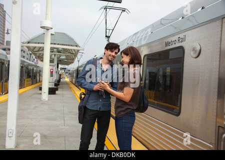 Couple listening to shared earphones at station, Los Angeles, California, USA - Stock Photo