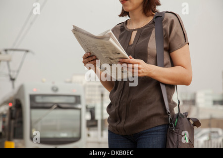Commuter reading newspaper whilst waiting at station, Los Angeles, California, USA - Stock Photo