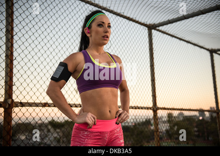 Female runner with hands on hips listening to mp3 player - Stock Photo