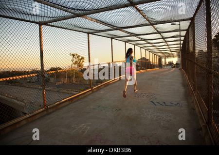 Female jogger running on walkway - Stock Photo