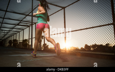 Female athlete running along walkway - Stock Photo