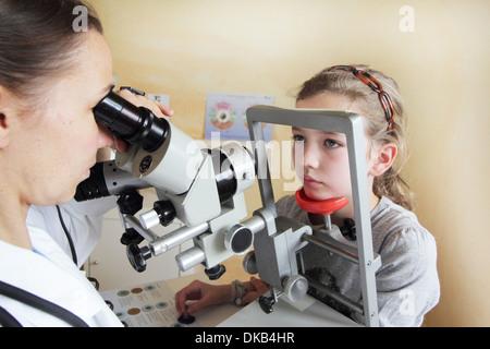 Optometrist examining girl's eyes - Stock Photo