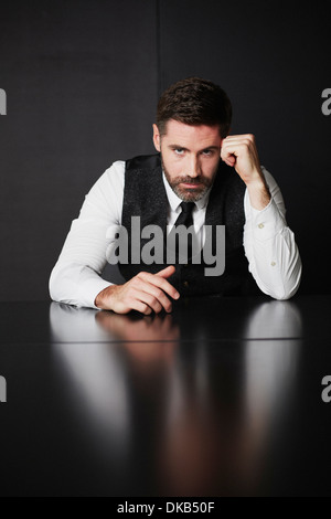 Businessman wearing waistcoat and shirt leaning on elbow - Stock Photo