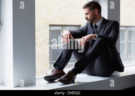Portrait of businessman sitting on windowsill looking out of window - Stock Photo