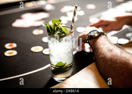 Cropped image of gambling table with playing cards, chips and cocktails - Stock Photo