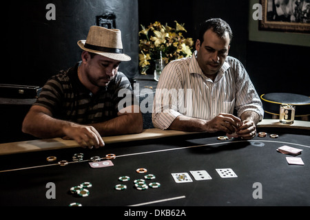 Mid adult men playing poker and drinking cocktails - Stock Photo