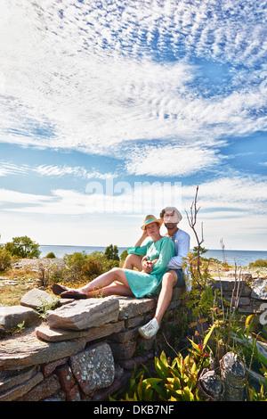 Couple sitting on stone wall, Eggergrund, Sweden - Stock Photo
