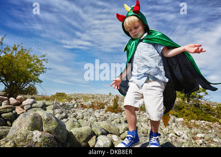 Boy wearing green cape walking on pebbles, Eggergrund, Sweden - Stock Photo