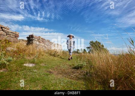 Boy wearing pirate costume running along grass, Eggergrund, Sweden - Stock Photo