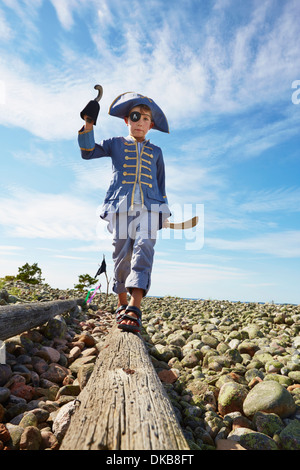 Boy dressed as pirate on log on beach, Eggergrund, Sweden - Stock Photo