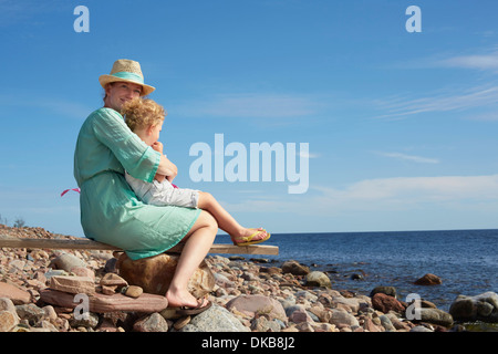Mother and daughter sitting on beach, Eggergrund, Sweden - Stock Photo