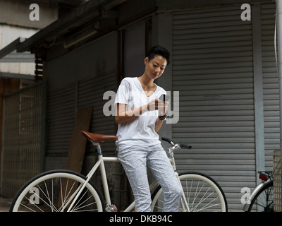 Young woman leaning against bicycle, using smartphone - Stock Photo