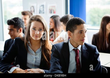 Teenage schoolchildren in classroom - Stock Photo