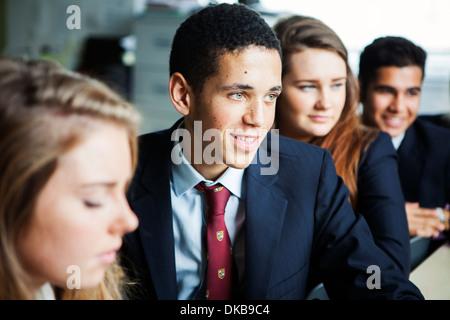Teenage schoolchildren sitting at desks - Stock Photo