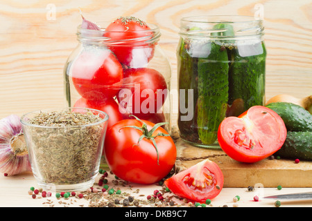canned tomatoes and cucumbers in glass jar, homemade preserved vegetables - Stock Photo