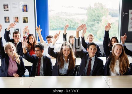 Teenage schoolchildren with hands raised in classroom - Stock Photo