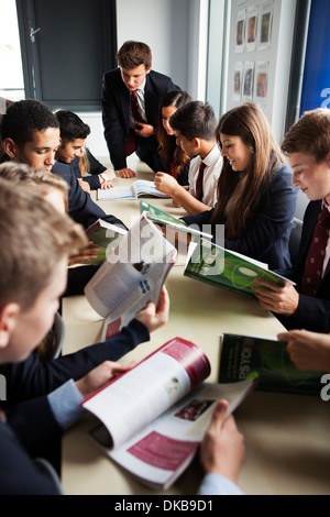 Teenage schoolchildren looking at textbooks in class - Stock Photo