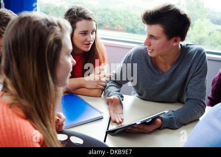 Teenage schoolchildren sitting at desk using digital tablet - Stock Photo