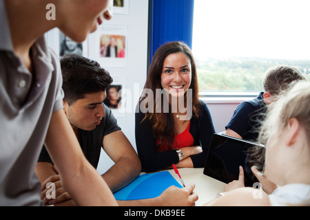 Teenage schoolchildren using digital tablet - Stock Photo