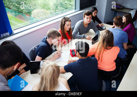 Teenage schoolchildren working together with digital tablet - Stock Photo
