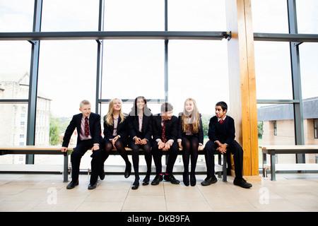 Portrait of teenage schoolchildren sitting in corridor Stock Photo