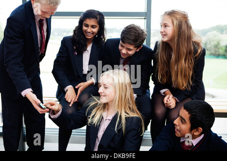 Group of teenage schoolchildren looking at mobile phone - Stock Photo