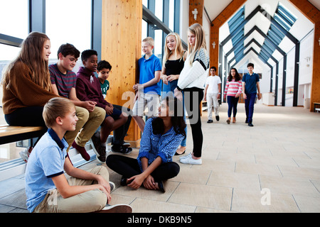 Group of  teenage schoolchildren sitting chatting in corridor - Stock Photo