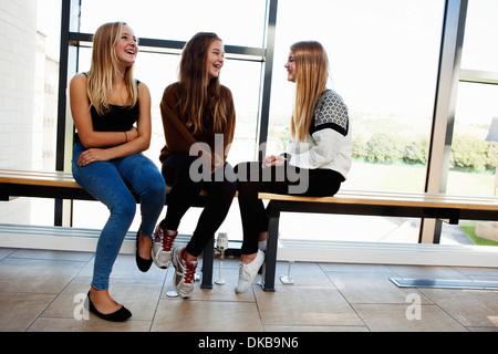 Three teenage schoolgirls sitting chatting in corridor - Stock Photo