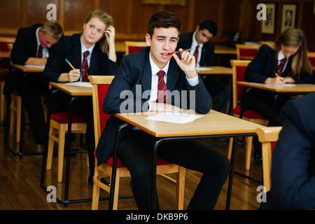 Group of  teenage schoolchildren sitting examination - Stock Photo