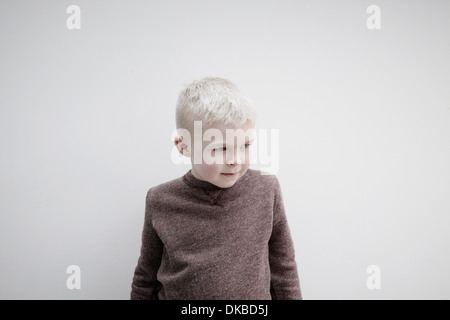 Portrait of boy wearing brown jumper, looking away - Stock Photo