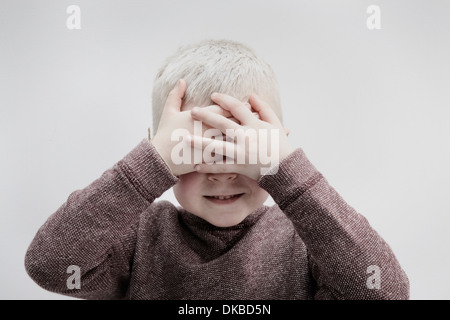 Portrait of boy wearing brown jumper, covering face with hands - Stock Photo