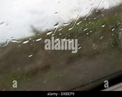 Water drops on the glass front of the car on a rainy day in autumn - Stock Photo
