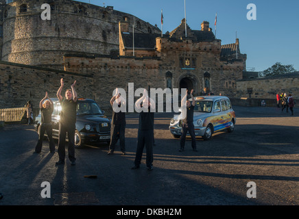 Cabbies from the Central Taxi company in Edinburgh, Scotland, dance for a company tv advertisement in front of castle. - Stock Photo