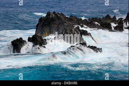 Madeira Portugal. The Atlantic ocean crashing waves over the rocky coastline - Stock Photo
