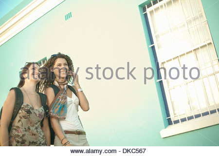 Young women walking past pastel painted house - Stock Photo