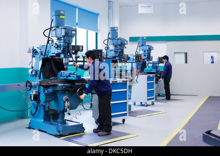 Workers at small parts manufacturing factory in China - Stock Photo