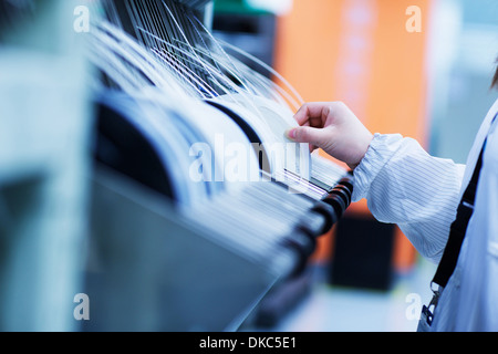 Worker at small parts manufacturing factory in China - Stock Photo