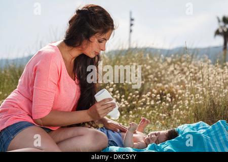 Mother applying suncream to baby's chest - Stock Photo