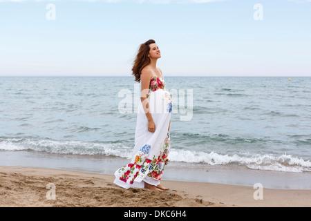 Pregnant woman walking along beach - Stock Photo