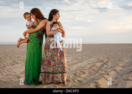 Mothers standing on beach holding baby and toddler - Stock Photo