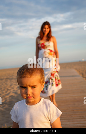 Toddler standing on boardwalk, mother in background - Stock Photo