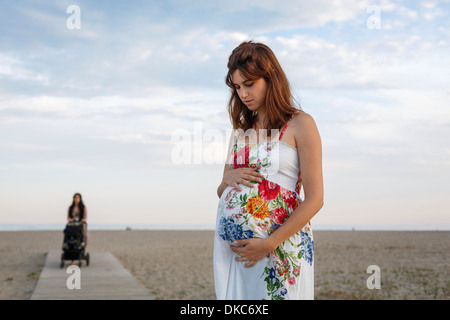 Pregnant woman standing on boardwalk, woman pushing pushchair in background - Stock Photo